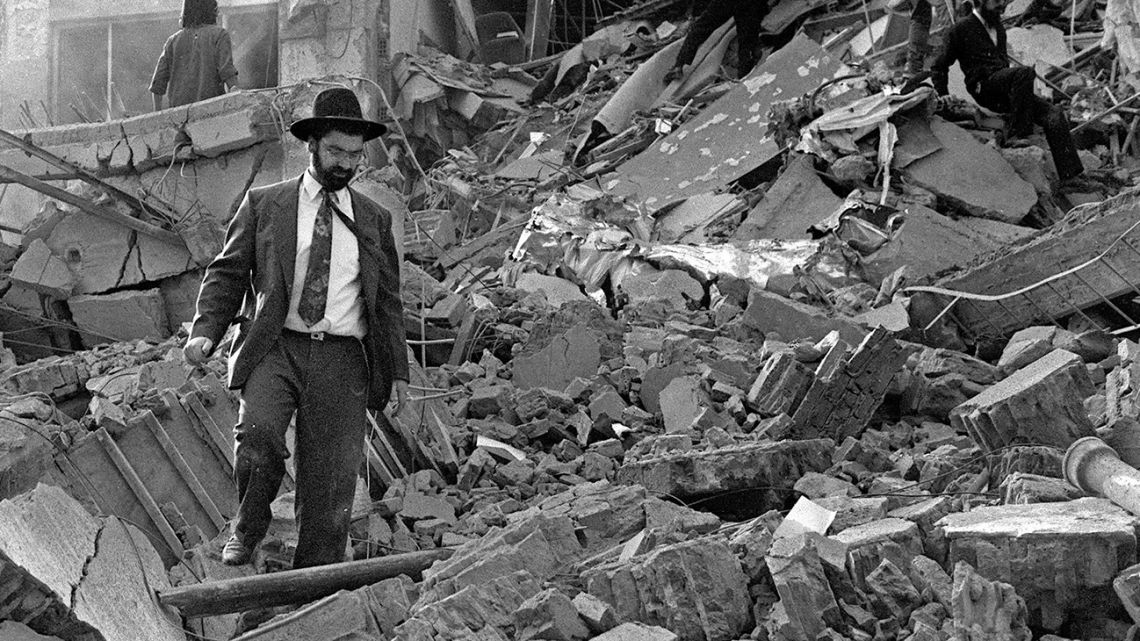 In this file photo taken on July 18, 1994, a man walks over the rubble left after a bomb exploded at the Argentinian Israeli Mutual Association (AMIA in Spanish) Jewish community centre in Buenos Aires. Twenty-five years have passed since the explosion, which caused 85 deaths.