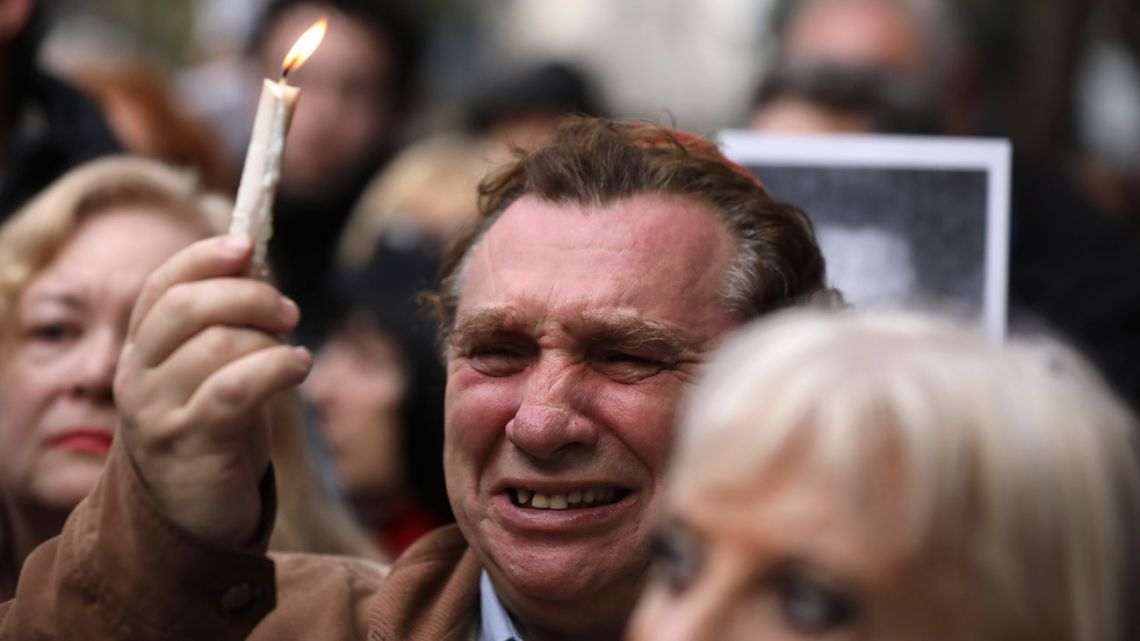 A man cries as he holds up a candle on the 25th anniversary of the bombing of the AMIA Jewish community centre, an attack that killed 85 people.