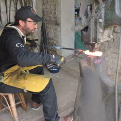 Cristian Gentiletti prensando el milhojas de acero para forjar Damasco.