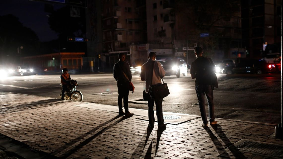 People wait for a public transportation on a street during a blackout in Caracas, Venezuela, Monday, July 22, 2019.