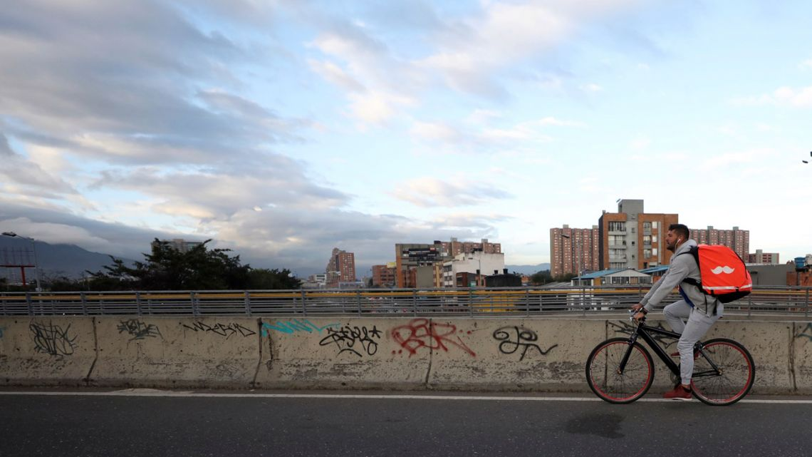 Venezuelan bicycle courier Samuel Romero pedals through Bogotá, Colombia, at the start of his work day on Wednesday, July 17, 2019. Critics of the app say that a large number of couriers have basically become full-time workers, and lawmakers in Colombia and Argentina are considering regulations to boost protection for the workers.