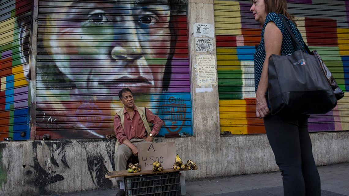 A street vendor sells bananas in front of a painting with the image of Venezuelan Independence hero Simon Bolívar, in Caracas, Venezuela, Tuesday, July 16, 2019.
