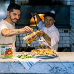 Leandro Barroso, chef ejecutivo de Paesano Rosso, dándole los últimos toques a una vera pizza napoletana. Trajeron el horno pizzero desde la propia Nápoles.