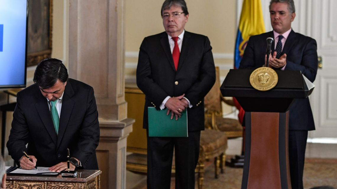 The head of the Colombian National Registration Office of Civil Status Juan Carlos Galindo (left) signs a decree that allows the nationalisation of 24,000 children of Venezuelan parents born in Colombia next to Colombian Foreign Minister Carlos Holmes Trujillo (centre) and Colombian President Iván Duque, in Bogotá.
