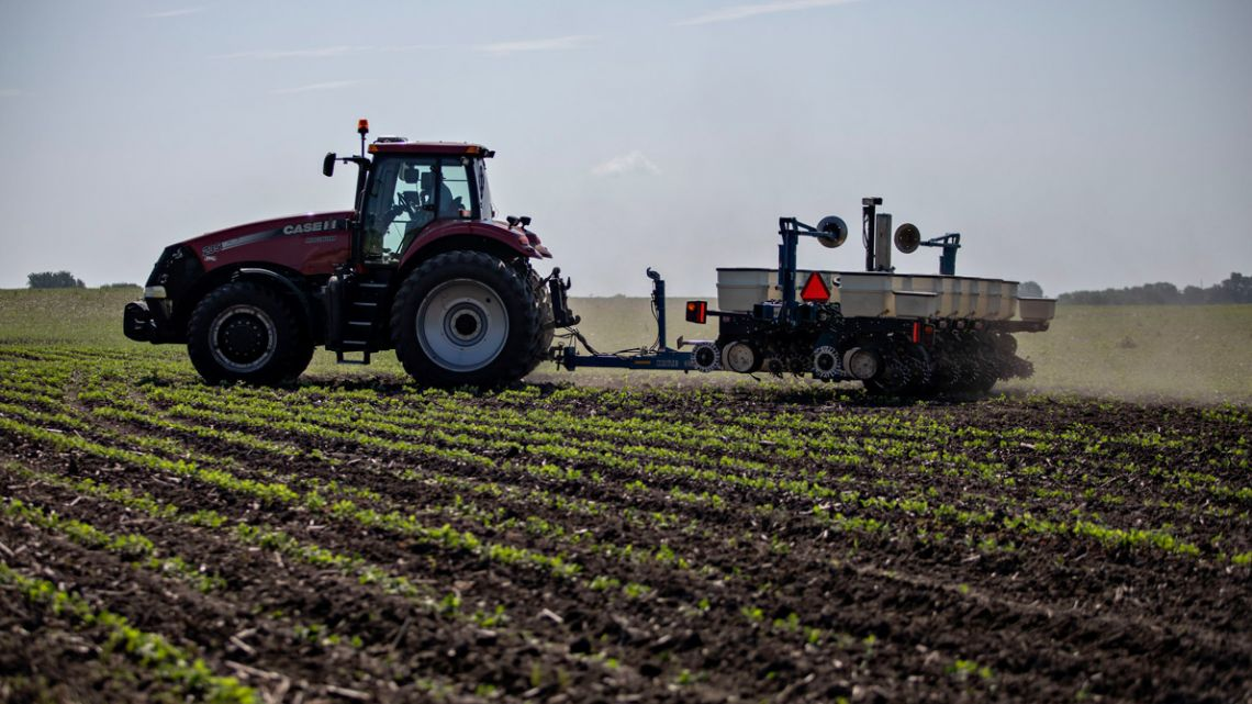 A farmer pulls a planter through a soybean field at a farm field near Buda, Illinois.