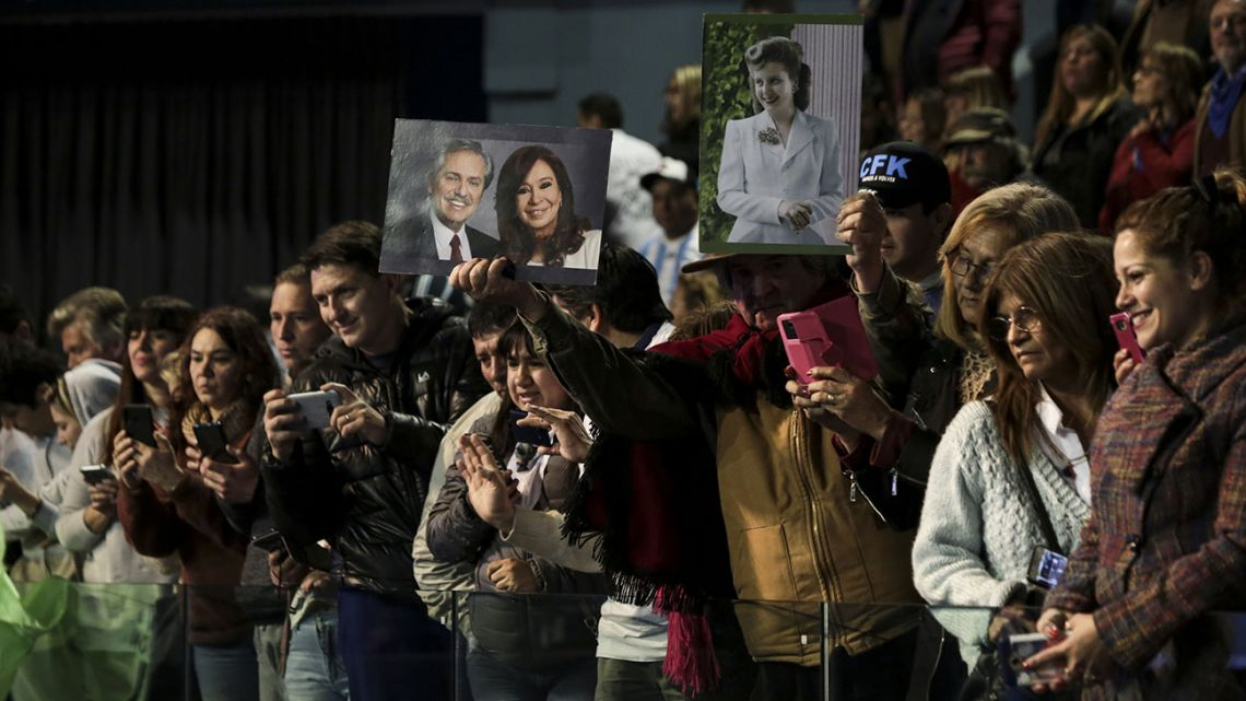 Attendees hold images of Alberto Fernandez, presidential candidate for the Citizen's Unity Party, from left, Cristina Fernandez de Kirchner, Argentina's former president and vice presidential candidate, and former Argentine first lady Eva Perón ahead of a book presentation by Kirchner at DirecTV Arena in Tortuguitas, Argentina, on Saturday, Aug. 3, 2019.