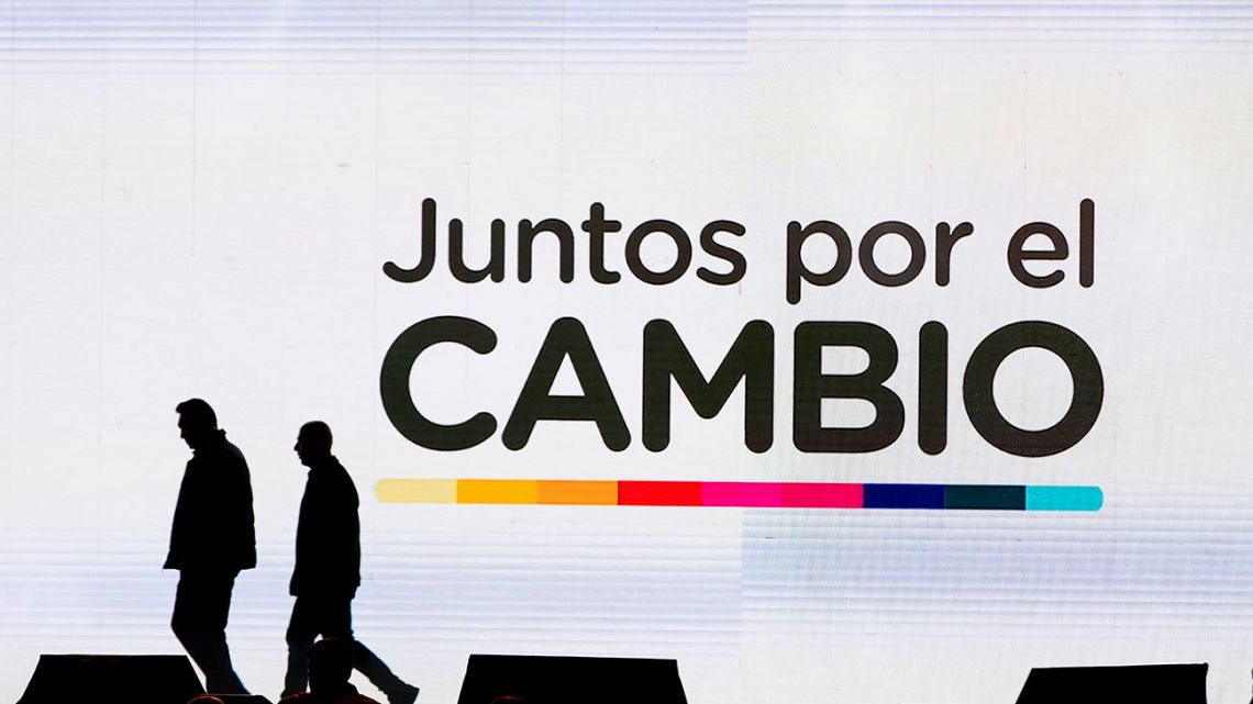 "Men walk at the ruling party's ""Juntos por el Cambio"" stage at party headquarters as they wait for the results of primary elections in Buenos Aires."