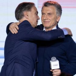 President Mauricio Macri, right, embraces his running-mate Miguel Angel Pichetto at their party's headquarters after primary elections in Buenos Aires, Argentina.