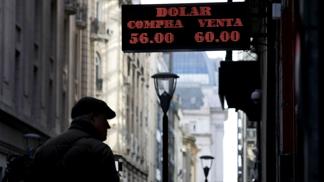 Man looks at rates posted on a currency exchange in Buenos Aires.
