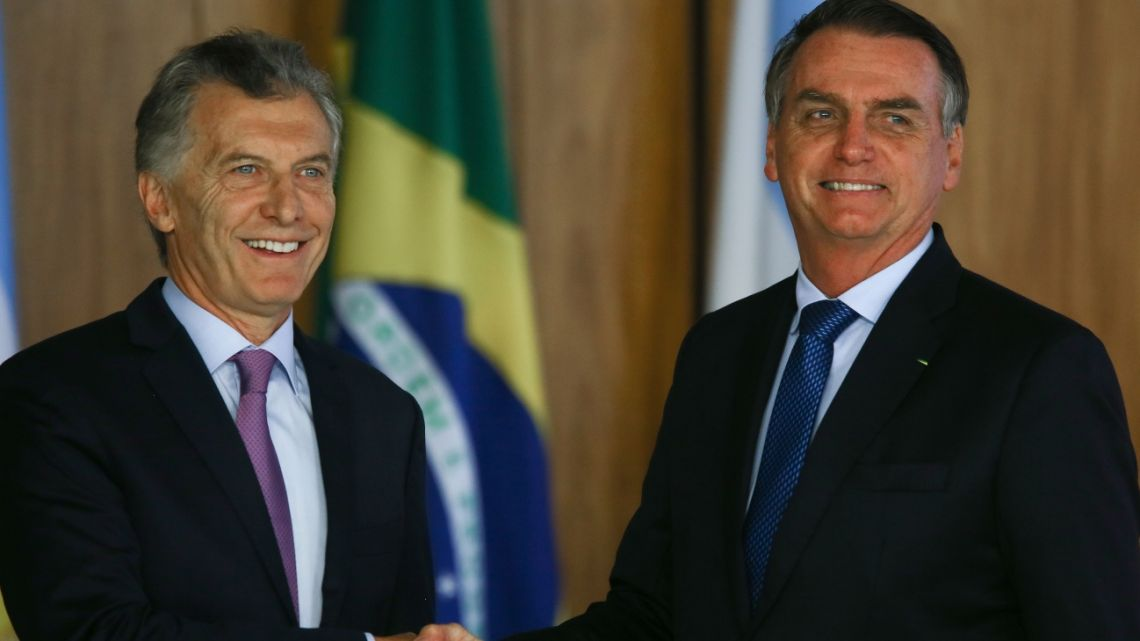 Jair Bolsonaro shakes hands with Mauricio Macri during a joint news conference in Brasilia, Brazil, on Wednesday, Jan. 16, 2019.