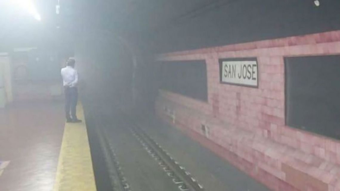 A man watches smoke fill the San José station of the Subte E line.