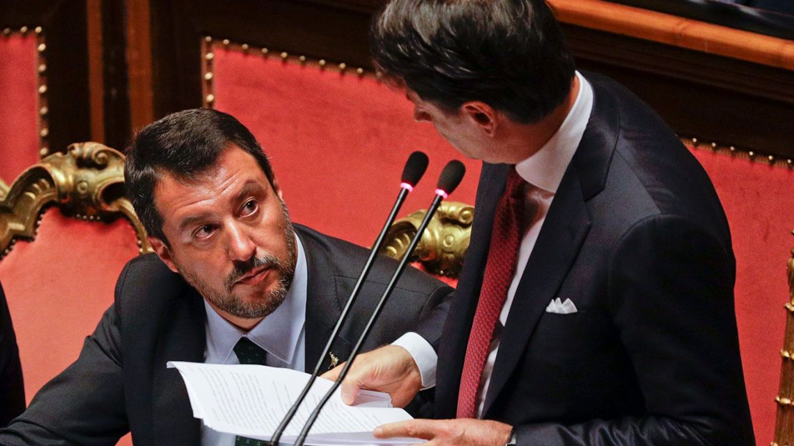Italian Premier Giuseppe Conte, right, looks at Deputy-Premier Matteo Salvini as he addresses the Senate in Rome, Tuesday, Aug. 20, 2019.