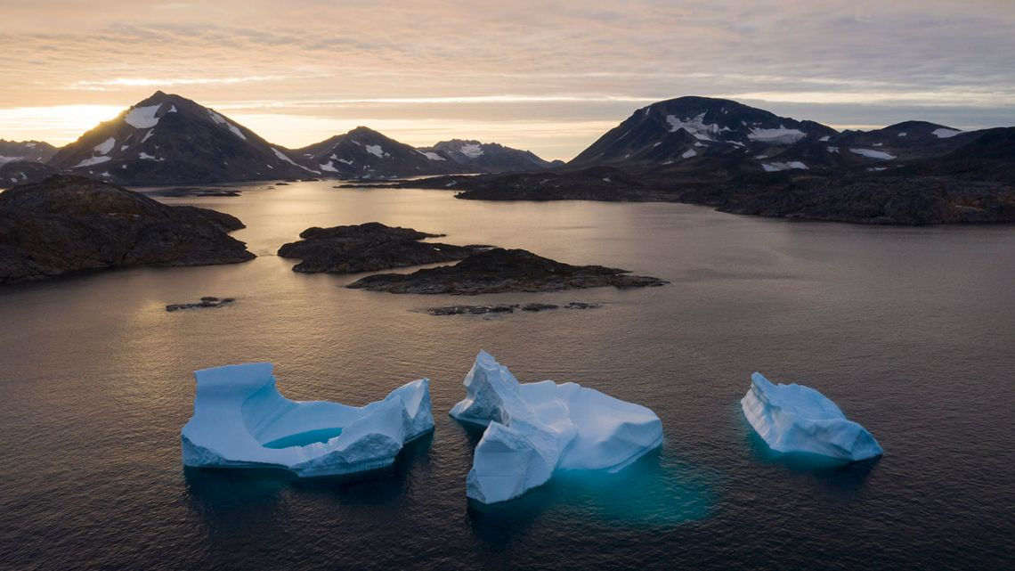 In this Aug. 16, 2019, photo, large Icebergs float away as the sun rises near Kulusuk, Greenland. Scientists are hard at work, trying to understand the alarmingly rapid melting of the ice.