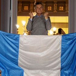 President Mauricio Macri greets supporters from the balcony of government house, in Buenos Aires.