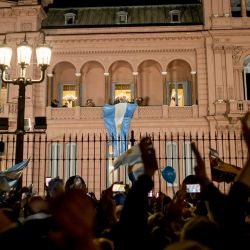 Supporters of President Mauricio Macri wave during a march in support of the government. The president stands on the balcony of the Casa Rosada, with his wife Juliana Awada.