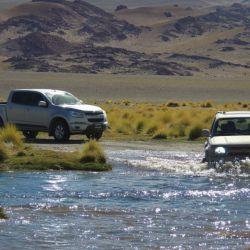 Las camionetas atraviesan el río Los Patos con bastante nivel de agua.
