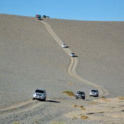 La caravana serpentea por la caldera del volcán, entre formaciones de tosca.