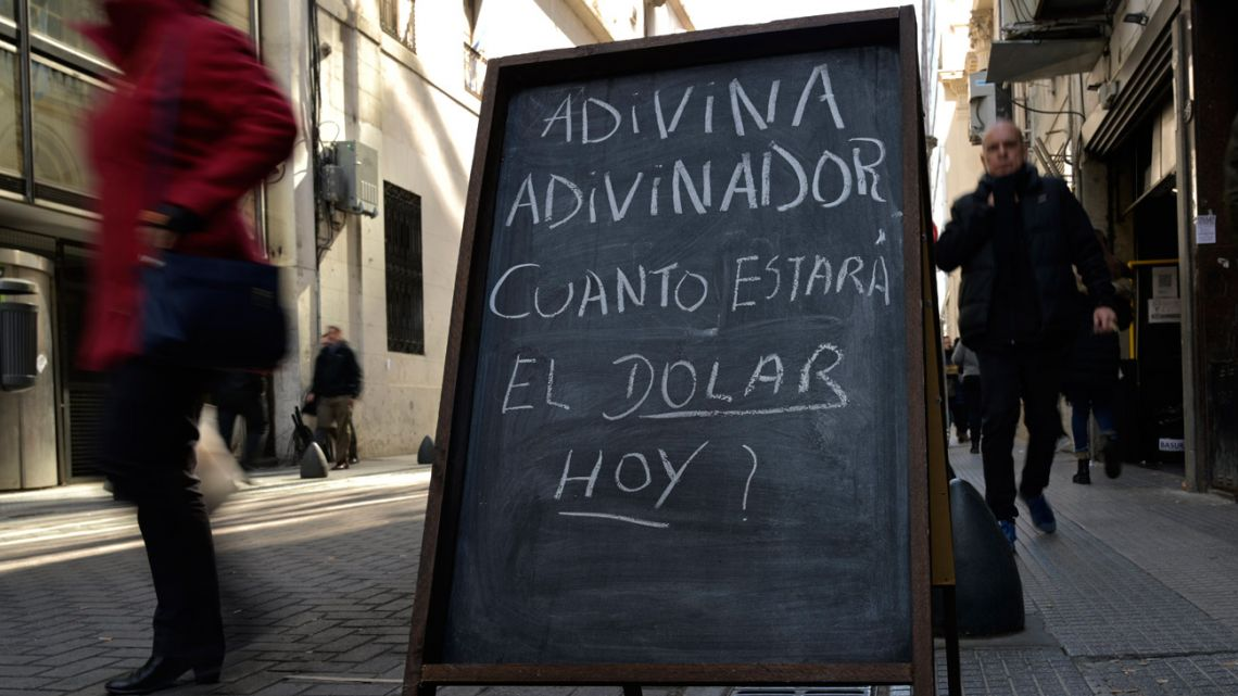 A chalkboard with a riddle about guessing the day's price of the US dollar is seen in the financial district of Buenos Aires.
