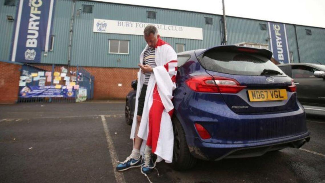 A devastated fan stands outside Bury Football Club's stadium.