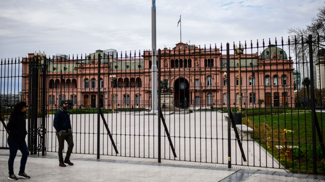 People walk in front the Casa Rosada.