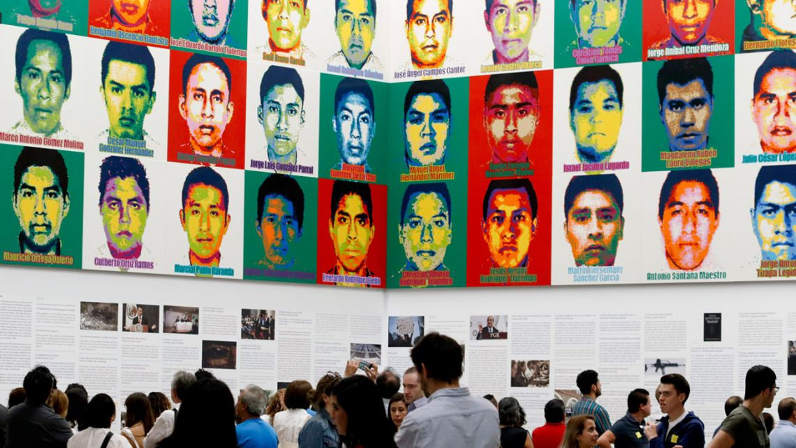 In this April 13, 2019 file photo, people stand under the portraits of 43 disappeared teachers' college students, by Chinese concept artist and government critic Ai Weiwei at the Contemporary Art University Museum, in Mexico City.