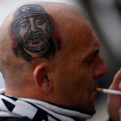 A fan shows off a freshly-inked tattoo of Diego Maradona – on his head.
