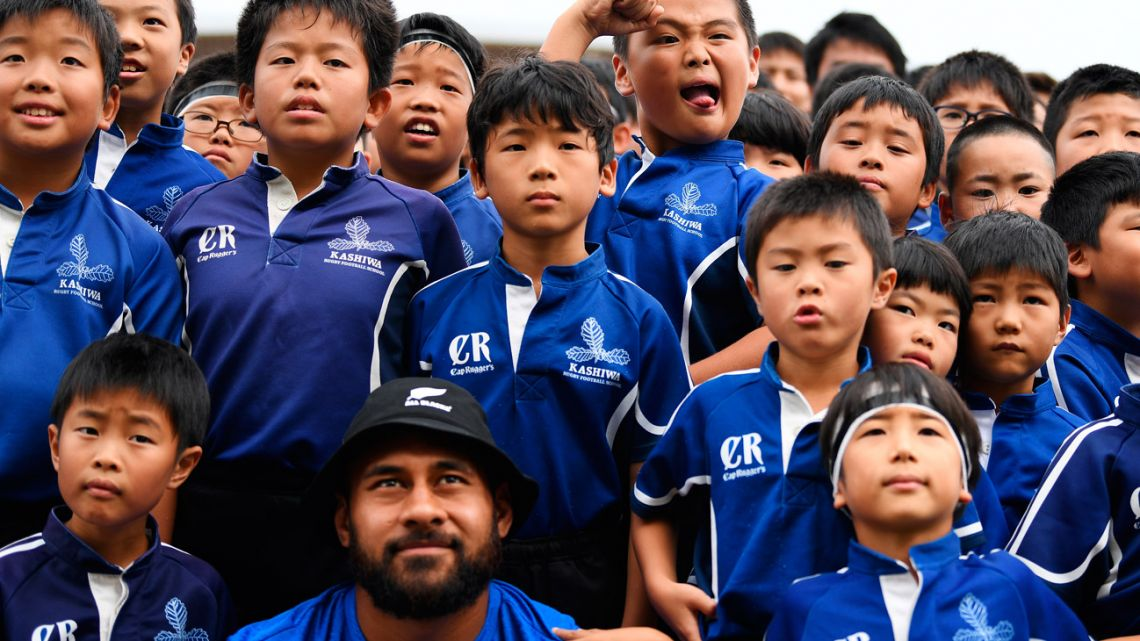 Children pose for a photo with several New Zealand rugby team players during a fan event at Kashiwanoha Park Stadium in Kashiwa, Chiba prefecture, on September 14, 2019, ahead of the 2019 Rugby Union World Cup which begins on September 20.