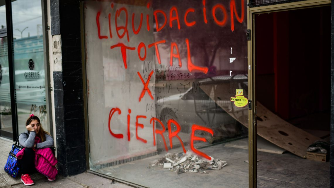 A woman sits outside a closed store closed in Trelew, in the Patagonian province of Chubut.