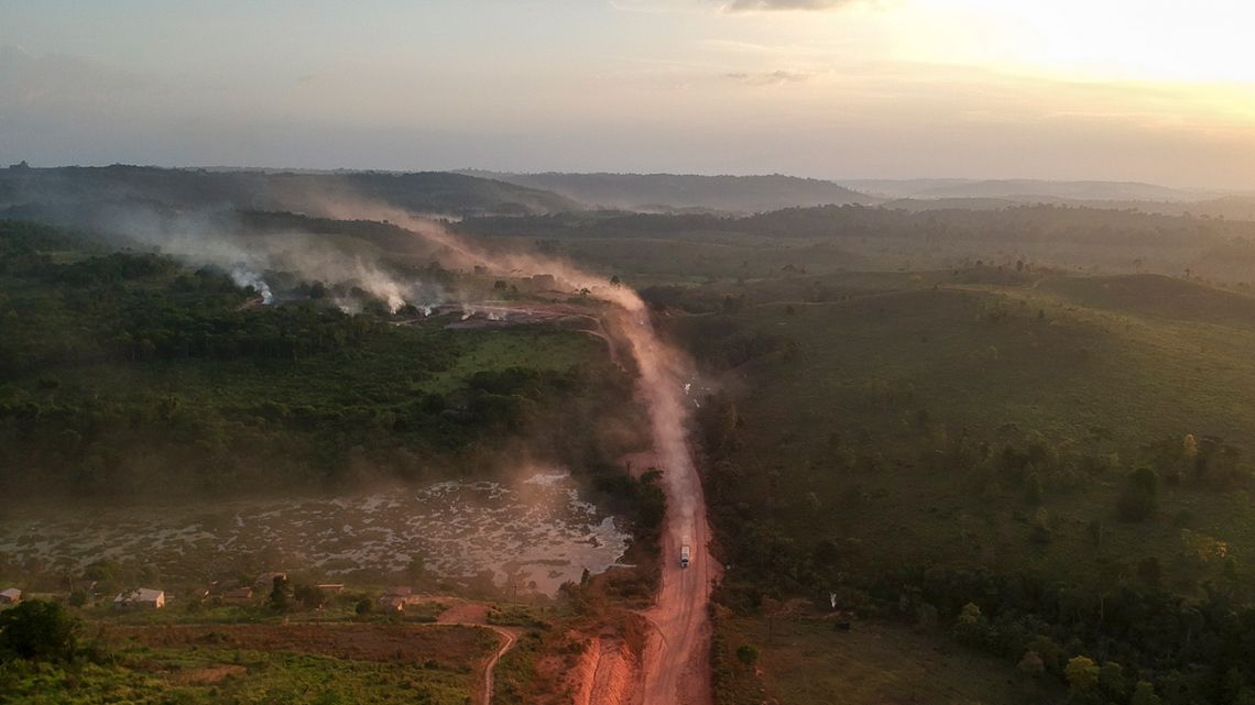 In this aerial view the red dust of the BR230 highway, known as 'Transamazonica,' mixes with fires at sunset in the agriculture town of Ruropolis, Para state, northen Brazil, on September 6, 2019.