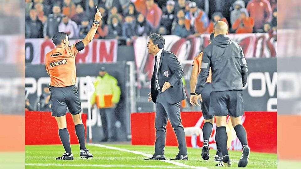 Espalda. Merlos amonesta a Gallardo. Después le cobró a Vélez un penal inexistente.