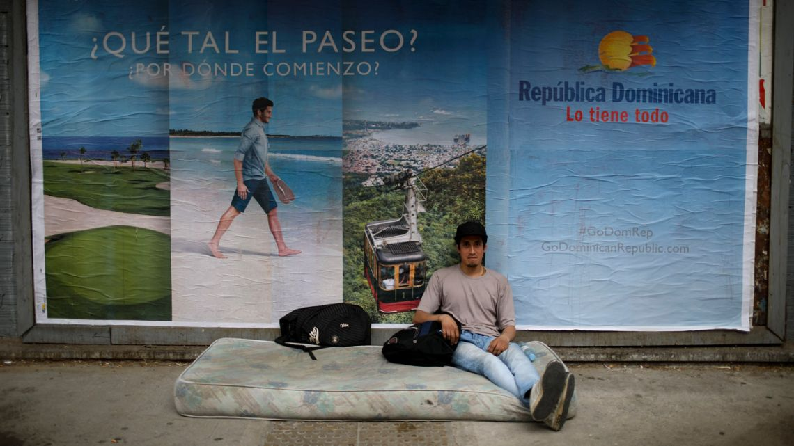 Jesús Leonel Vallejos, who lost his job as an upholsterer when the factory he worked at closed, sits homeless on a street in Buenos Aires.