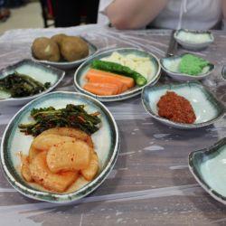 Kimchi y otras verduras salteadas para acompañar a los pescados y mariscos frescos que se comen en el primer piso del mercado.
