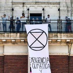 Protestors display a banner reading 'Climate and ecological emergency' at the Torre Monumental during a demonstration called by climate change activist group Extinction Rebellion.