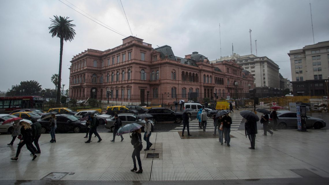 Pedestrians carry umbrellas while walking past the Casa Rosada.