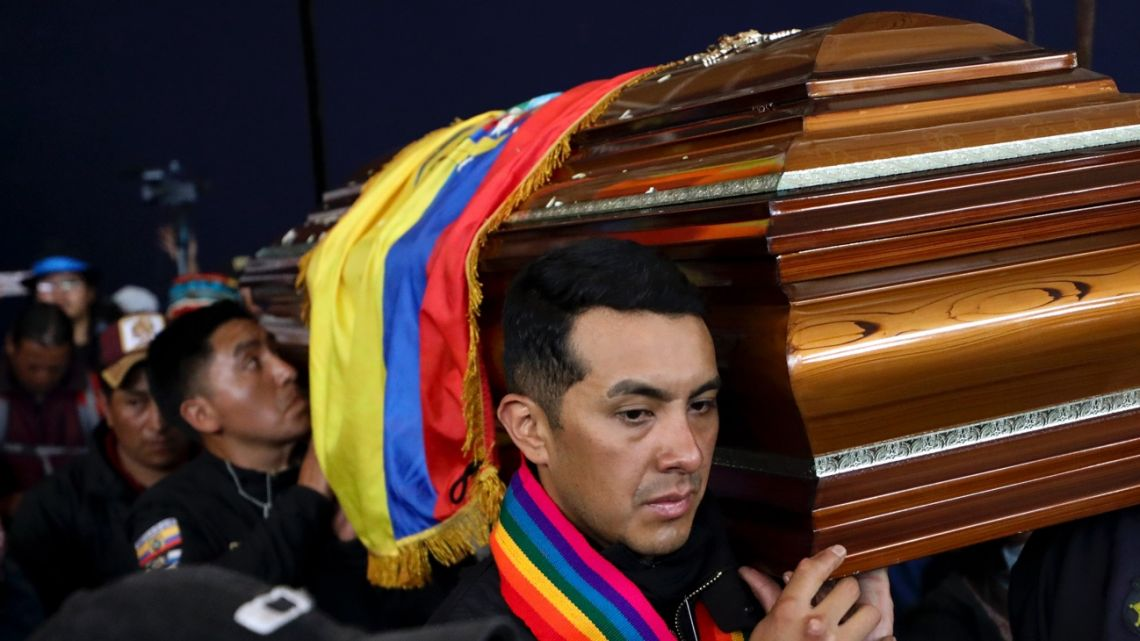 Police held captive by anti-government protesters, are forced to carry a coffin that contain the remains of a companion who protesters say died during yesterday's national strike, in a procession inside the Casa de Cultura in Quito, Ecuador.