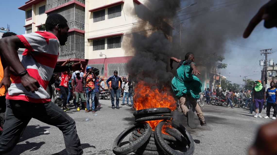 Demonstrators jump over a burning barricade during anti-government protests in Port-au-Prince.