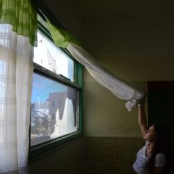 Flor Toledo, 17, looks through a damaged window at Escuela 712 in Trelew.