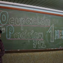 "Lautaro Iparraguirre, 17, stands alongside a chalkboard reading ""Peaceful Occupation for One Month"" at Escuela 712, a public school occupied by students in the city of Trelew in Chubut province."