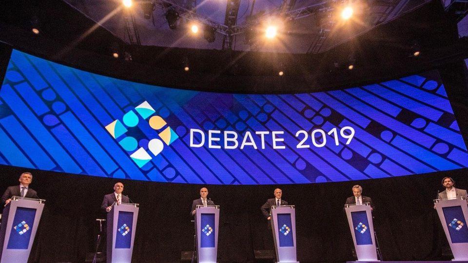 Los candidatos en el escenario debaten sus propuestas.