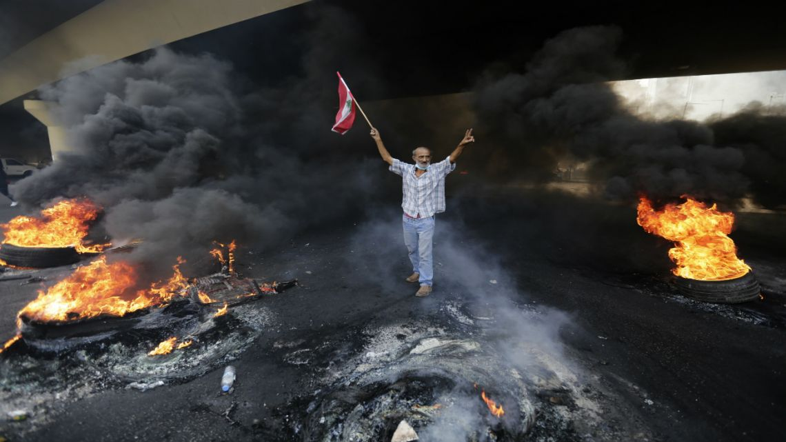 An anti-government demonstrator walks through the wreckage that's been caused by protests. Holding a Lebanese national flag, he calls for the government to remove the new taxes.