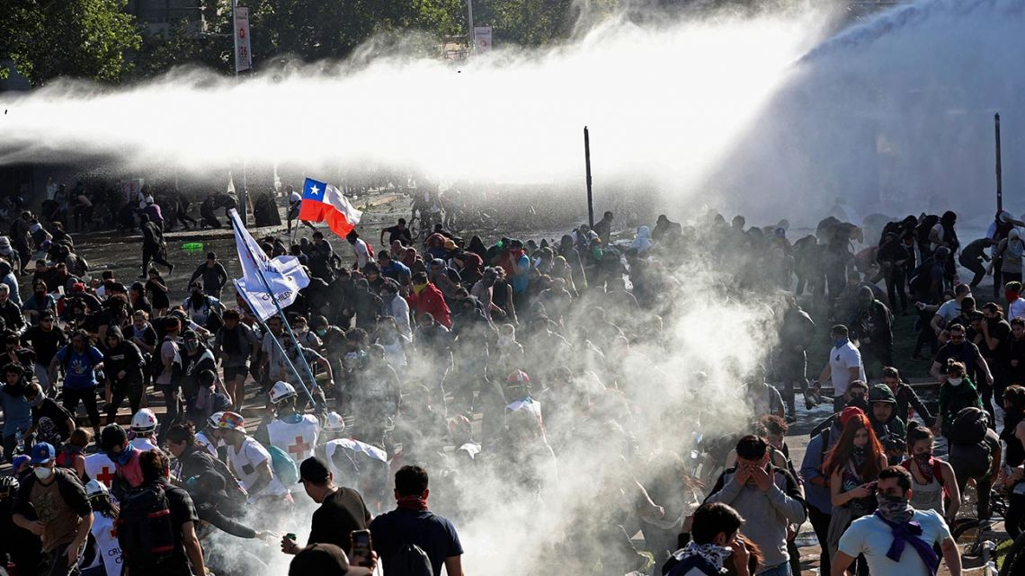 Demonstrators run from police launching water canons and tear gas as a state of emergency remains in effect in Santiago, Chile, Sunday, October 20, 2019.