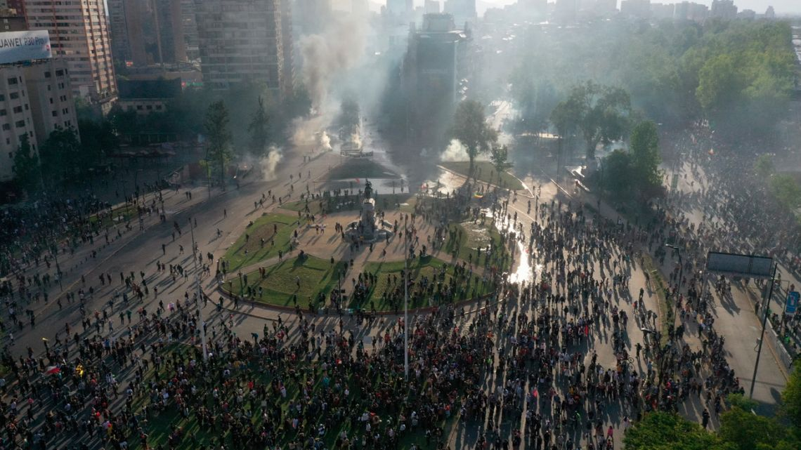 In this aerial view, demonstrators clash with riot police at Plaza Italia square in Santiago, Chile, on October 21, 2019, for a fourth straight day as part of protests in Chile.