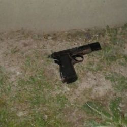 A gun (pictured, identified as a 9mm pistol) was among items seized from the assailants, who allegedly beat the homeowner causing minor injuries. Picture released to Perfil.com.