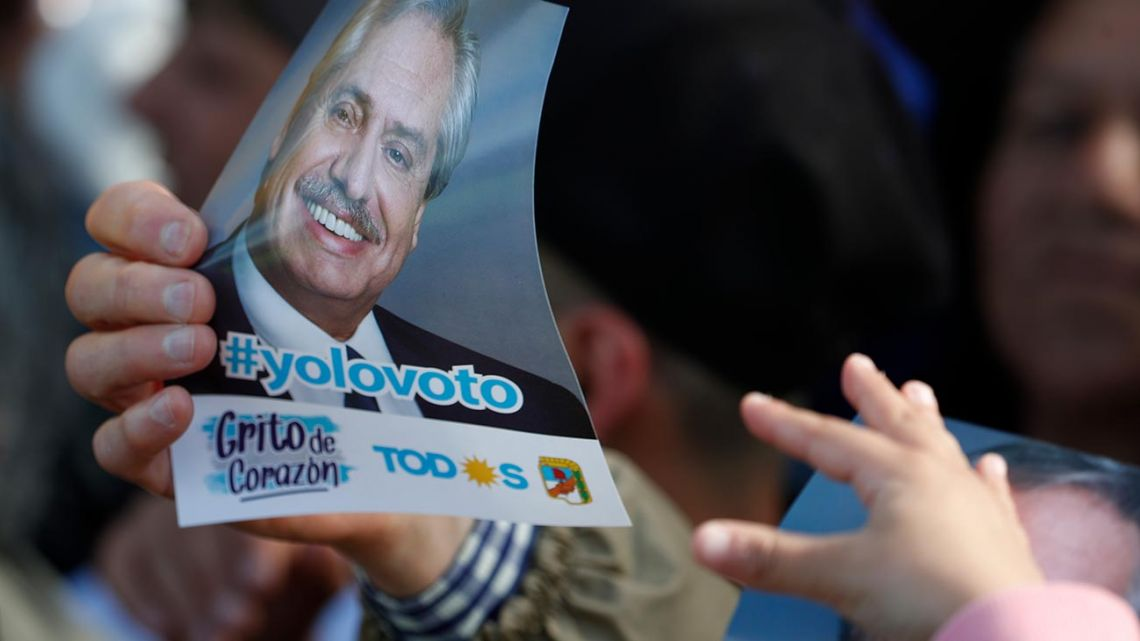 A suppporter of presidential candidate Alberto Fernández holds up a flyer bearing his image, during a campaign rally in Mar del Plata yesterday.