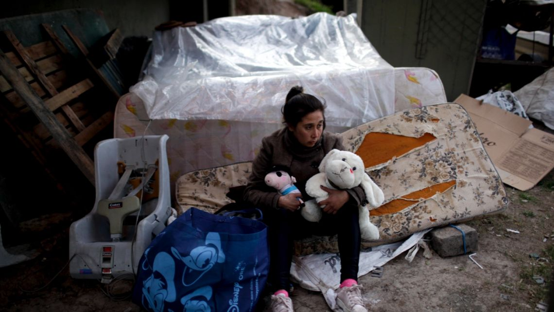 Macarena Contreras holds stuffed animals she plucked from the garbage for her three children.