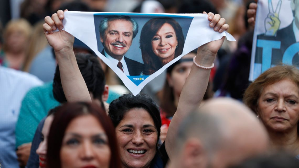 A supporter of presidential candidate Alberto Fernández and his running-mate former president Cristina Fernández de Kirchner holds up a scarf bearing their image.