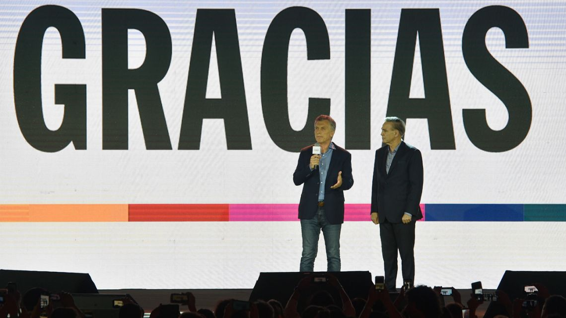 President Mauricio Macri concedes defeat on stage, flanked by his running-mate Miguel Ángel Pichetto.