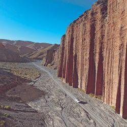 Toma a vuelo de dron del rojo farallón de Cabrerías, con una altura superior a 120 metros hace que los vehículos transitando a sus pies parezcan pequeños.