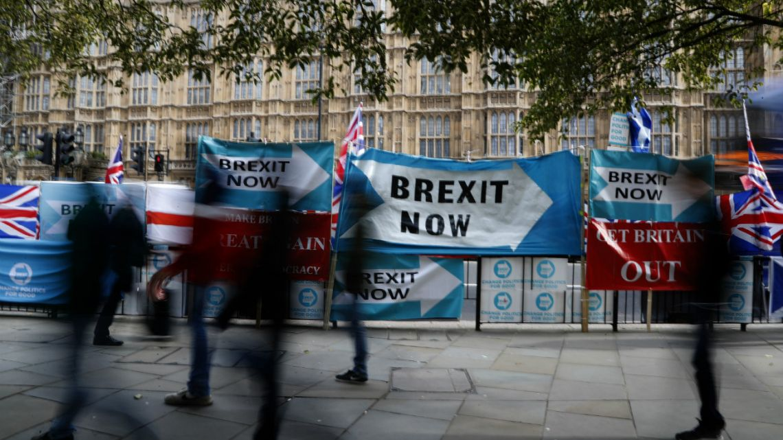 Pedestrians pass Brexit banners opposite parliament in London