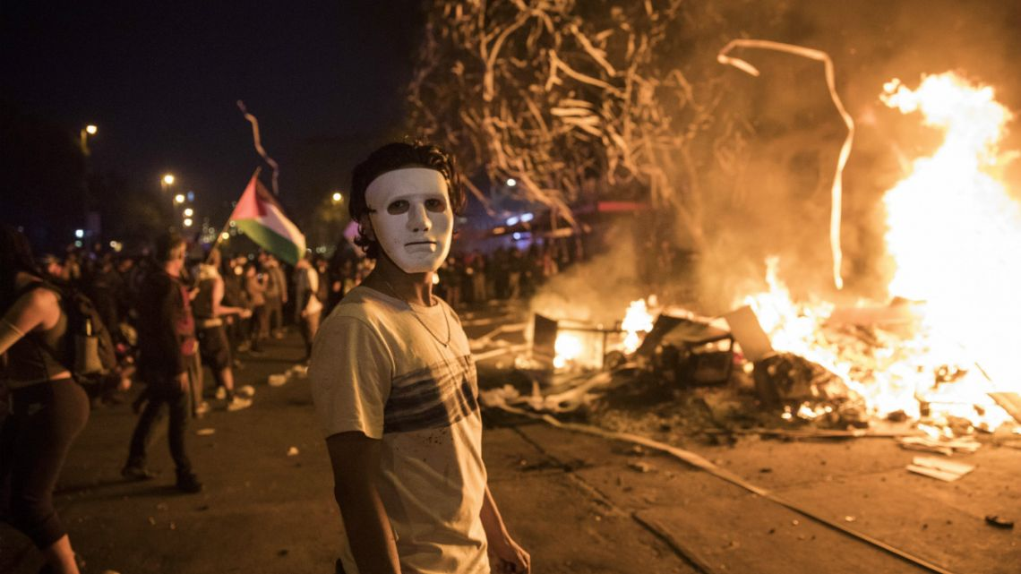 A masked anti-government protester stands by a burning barricade in Santiago, Chile,